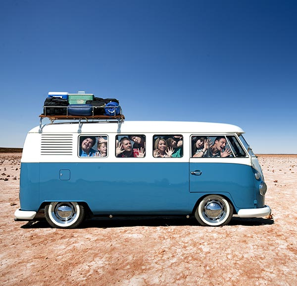 Family and friends all laughing and smiling squashed into a 1960s Volkswagen Kombi Van with luggage on the roof
