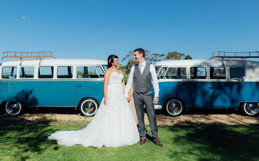 Bride & Groom in front of classic 1960s Volkswagen Kombi Vans restored for wedding day car hire