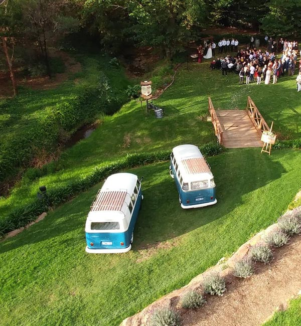 Aerial view two blue and white 1960s Volkswagen Kombi Vans at Wedding Ceremony available for wedding car hire